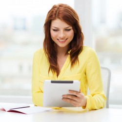 red haired woman sitting at desk looking at tablet